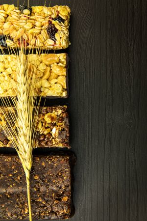 Granola bars with roasted nuts, selective focus. Oatmeal bar with nuts on black background. Nutrition for athletes. Vegetarian sweetness.