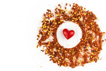 Hot spice. Chilli powder. Dried chili. Healthy spices. Spilled chili on white background. Stock fotó