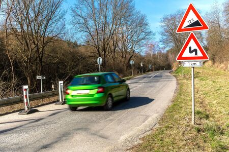 Car goes uphill. Road grade 12 per cent, road sign in Czech Republic near the village of Rikonin. Dangerous climb. Danger on the road. Traffic signs.