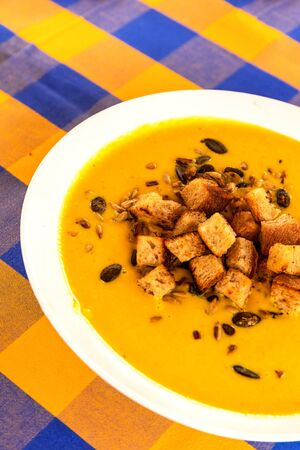 Vegetable Carrot Soup with Croutons and roasted seeds. Healthy vegan food. Cream soup.