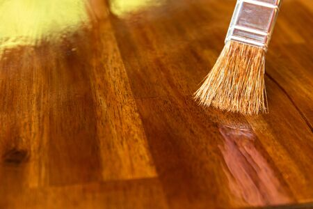 Applying protective oil on a wooden furniture. Varnishing the table top of acacia wood. Close-up view of a paintbrush. Housework. Imagens