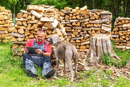 Man working in the woods with a tablet. Internet connection at work. The concept of modern technology.Working over the Internet. Banque d'images