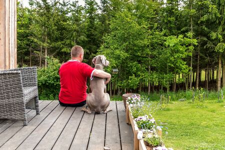 man is sitting with a dog on the terrace of the house and looking into the woods. Stock Photo