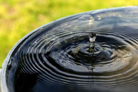Impact of a drop of rainwater on a full barrel. Saving water on the farm. Water for watering.