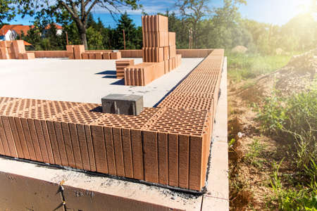 Construction site of a family house. Concrete base plate. Wall construction. Red bricks on a construction site. House construction. Imagens