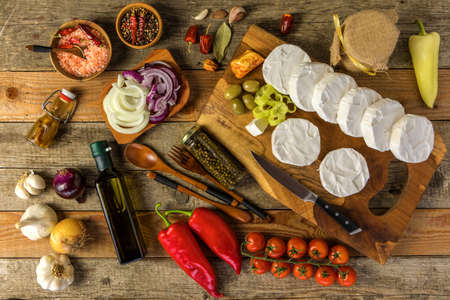 Homemade preparation of pickled cheese with chili peppers. Pickled cheese with herbs, olives. Camembert ready to pickle, sliced cheese covered with onions.