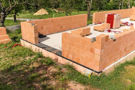 Construction of a small family house. House construction site. Brick wall on a construction site. A new house. Imagens