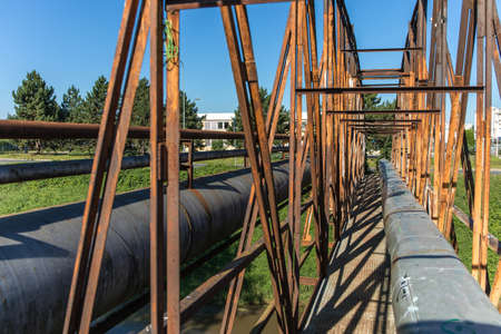 Old rusty iron bridge over the river with a steam pipeline. Heat supply. Industrial equipment.