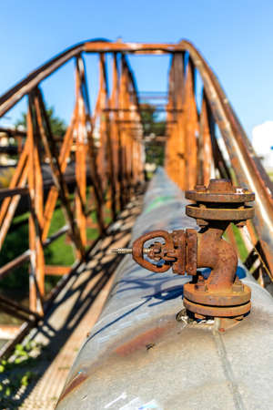 Old rusty iron bridge over the river with a steam pipeline. Heat supply. Industrial equipment. Detailed view of a steam pipeline valve.