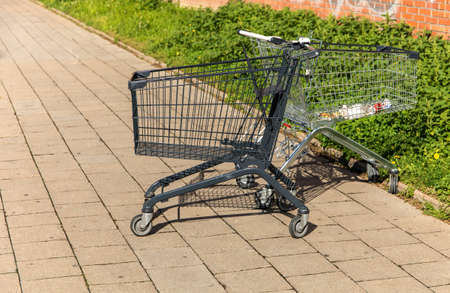 Shopping trolley in black on the street, on the sidewalk. Sidewalk in the parking lot next to the store. Shopping