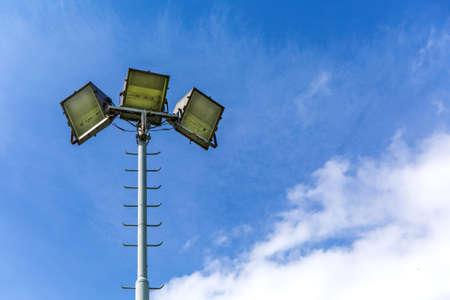 Reflector light for playground on blue sky background. Halogen light on metal pole. Stadium lights reflectors Imagens