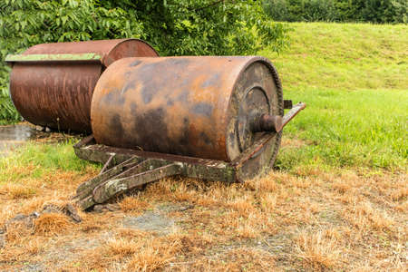 Soil roller for the handling and laying of the lawn. Old rusty metal lawn roller on some dry grass. Vintage roller for sports grounds football athletics etc. Imagens