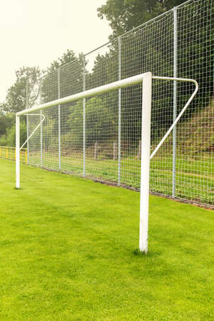 Empty football or soccer white gates. Soccer gate on green grassy field on a country playground.
