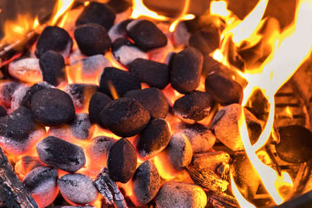 Top View Of Hot Flaming Charcoal Briquettes Glowing In The BBQ Grill Pit. Grill briquettes that are burning and waiting to be glowed for grilling.