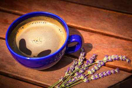 Cup of hot coffee and lavender on a wooden table. Aroma of coffee and lavender. Romantic morning. Standard-Bild