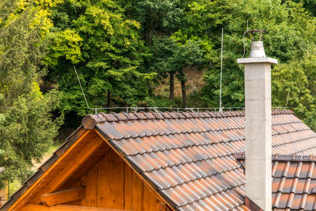 The roof of a family house with a chimney and a lightning conductor. Lightning protection. Detail of the roof.