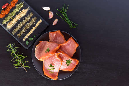 Top view raw pork chop steak on black wooden background. Pieces of raw pork steak with spices and herbs rosemary, thyme, basil, salt and pepper
