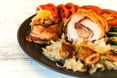Roasted Pork Roll stuffed with sausage wrapped bacon and Cheese. Pork roll with vegetable. Cabbage.