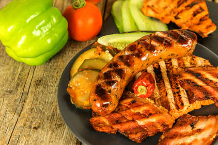 Grilled sausage and pork chops. Wooden background. Grilled meat. Unhealthy fatty food. Standard-Bild