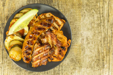 Grilled sausage and pork chops. Wooden background. Grilled meat. Unhealthy fatty food. 版權商用圖片