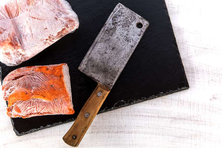Frozen raw pork neck chops meat steak isolated on slate. Frozen uncooked slices of beef steaks, tenderloin or rib eye with ice crystals on it.