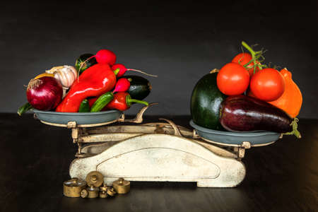Fresh vegetables and old kitchen scale on a black background. Harvest of vegetables. Healthy food.