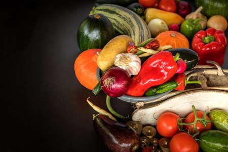 Fresh vegetables and old kitchen scale on a black background. Harvest of vegetables. Healthy food.
