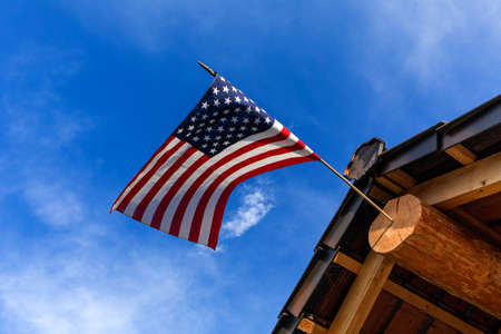 Log cabin roof & American Flag Against a Blue Sky. A red, white and blue American flag with stars and strips unfurled in the wind.
