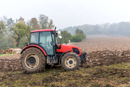 Red tractor on a muddy field. Agricultural work. Autumn foggy morning on the farm. Agriculture machinery.