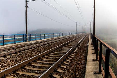 Railway tracks. Rail transport. Train transport. Autumn foggy morning. Rural landscape with railway tracks in the Czech Republic.