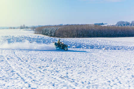 all terrain vehicle in motion at winter. Quad bikers on the march. Travel. Tourism. Quad bike driver riding over a frozen field in Czech Republic