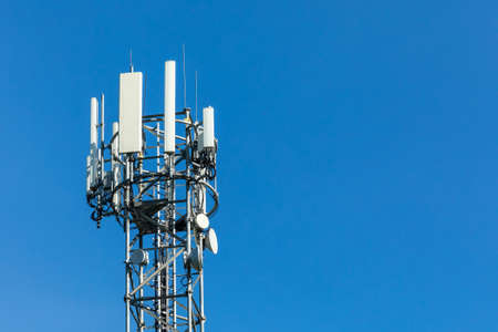 5G radio network telecommunication equipment with radio modules and smart antennas mounted on a metal on blue sky background.