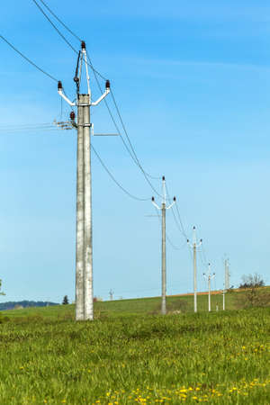 Power lines in the countryside against blue sky in spring day. Electricity distribution in the Czech countryside.