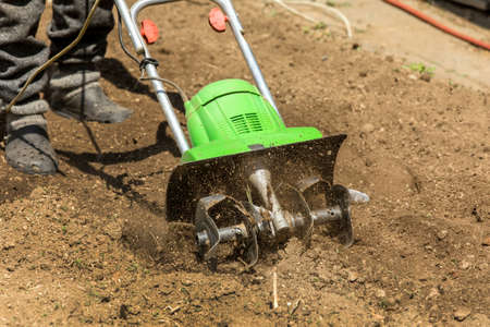 Gardening. Spring work on the farm. Land cultivation with an electric cultivator. Man plows the earth with an electric cultivator. Standard-Bild