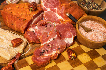 Meat, Pork neck in marinade and on a chopping boardon. Raw steak meat pork neck on chopping board with chili. Raw meat for grilling. Black background.
