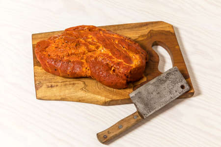 Meat, Pork neck in marinade and on a chopping boardon. Raw steak meat pork neck on chopping board with chili. Raw meat for grilling. White background. Standard-Bild