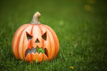 Pumpkin shaped ceramic candlestick on green grass. Funny Carved Pumpkin in the garden, halloween background Standard-Bild