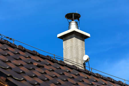 New modular ceramic chimney on the house roof with internet antenna. Roof of a detached house with a skylight and chimney against the sky