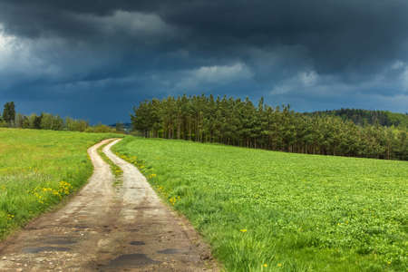 Road to the storm. Dark storm clouds and dirt road in Czech Republic. Spring stormy weather in the Czech countryside.
