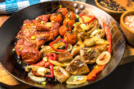 Meat, Pork neck in marinade and on a steel pan. Pork neck with baked potatoes and vegetables with chili.