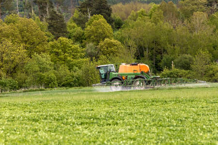 Tractor spray fertilize field with insecticide herbicide chemicals in agriculture field in Czech Republic. Spring overcast day. Agricultural chemistry.
