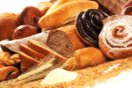 crus: Composition with bread and rolls in wicker basket, combination of sweet pastries for bakery or market with wheat Stock Photo
