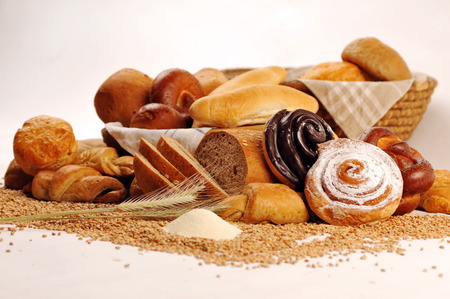 sweet pastries: Composition with bread and rolls in wicker basket, combination of sweet pastries for bakery or market with wheat Stock Photo
