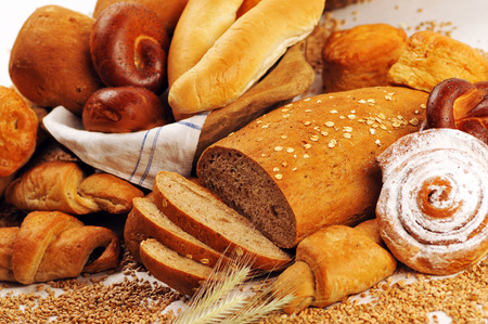 crus: Composition with bread and rolls in wicker basket, combination of sweet breads and pastries for bakery or market with wheat Stock Photo