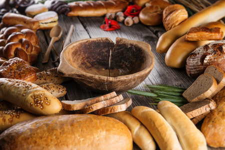 crus: Christmas cake, rolls and breads on wooden table with wooden bowl, background for bakery or market Stock Photo