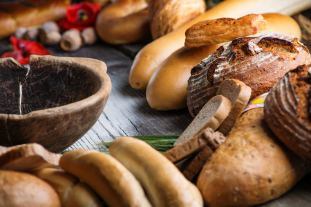 crus: rolls and breads on wooden table with wooden bowl, background for bakery or market Stock Photo