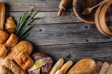 crus: baguette, rolls and breads on wooden table with wooden bowl, traditional bread, background for bakery or market