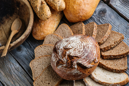 crus: Different bread and bread slices on wooden table, pastries combination, rye bread with grains, food background