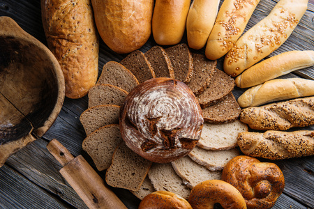 crus: rye bread and different slice of breads on wooden table, background for bakery or market