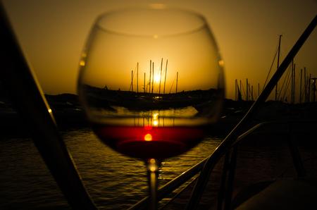 Sunset over marina with fine glass of wine